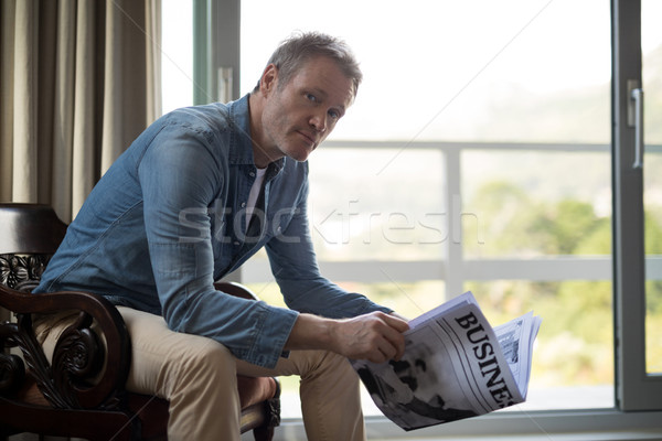 Stock photo: Man sitting on chair and reading newspaper in living room