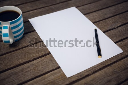 High agnle view of paper and fountain by coffee cup on wooden table Stock photo © wavebreak_media