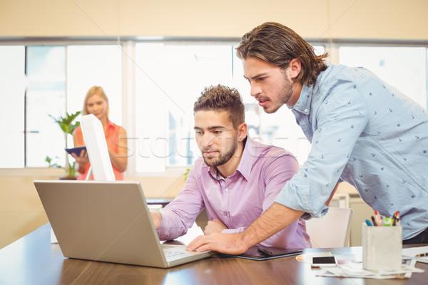 Businessmen working on laptop with female colleague in backgroun Stock photo © wavebreak_media