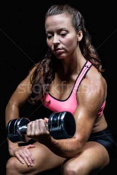 Thoughtful athlete sitting while lifting dumbbell Stock photo © wavebreak_media