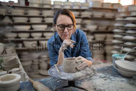 Female potter molding plate with hand tool Stock photo © wavebreak_media