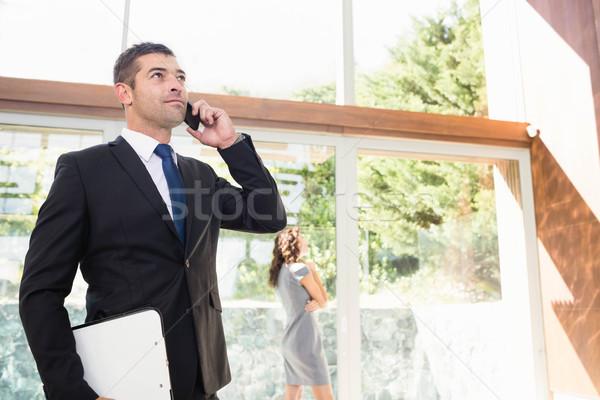 Agent mówić telefonu komórkowego klienta patrząc apartamentu Zdjęcia stock © wavebreak_media