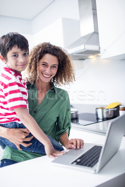 Mother using laptop with son in kitchen Stock photo © wavebreak_media