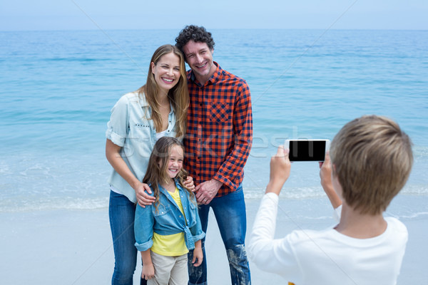 Boy photographing happy family at sea shore Stock photo © wavebreak_media