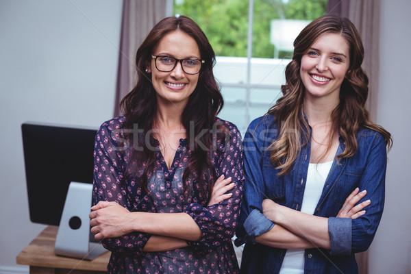 Portrait of beautiful women standing with arms crossed Stock photo © wavebreak_media