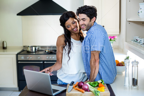 Young couple using laptop in kitchen Stock photo © wavebreak_media