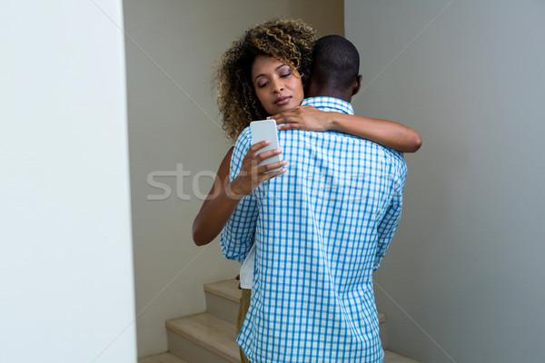 Nő mobiltelefon átkarol férfi otthon pár Stock fotó © wavebreak_media