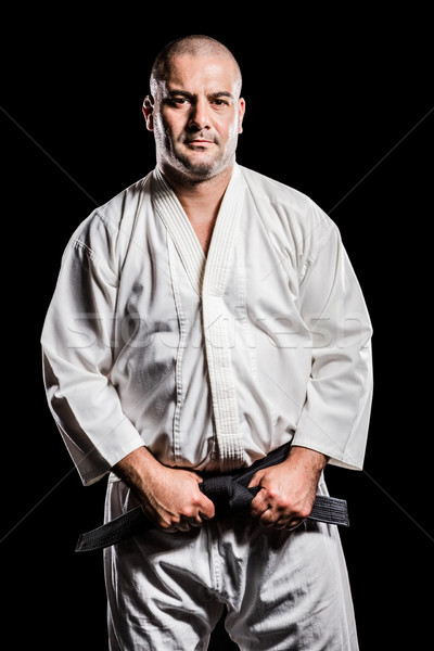 Fighter tightening karate belt Stock photo © wavebreak_media