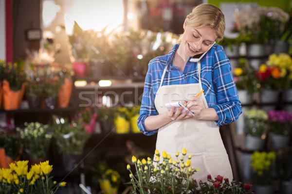 Kadın çiçekçi sipariş cep telefonu Stok fotoğraf © wavebreak_media