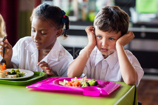 Thoughtful boy with classmates in canteen Stock photo © wavebreak_media