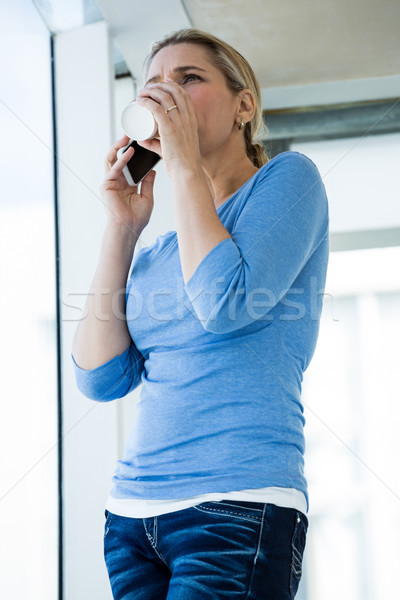 Low angle view of woman having drink while talking on phone Stock photo © wavebreak_media