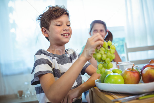 Smiling boy holding a bunch of grapes Stock photo © wavebreak_media