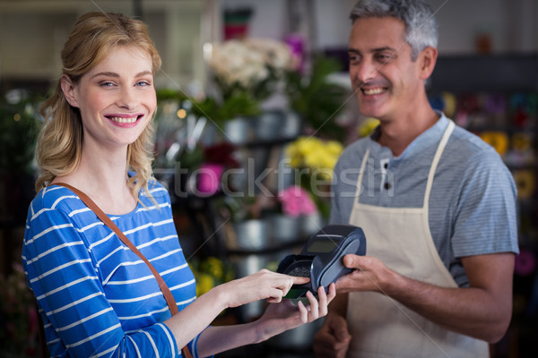 Smiling woman making payment with her credit card to florist Stock photo © wavebreak_media