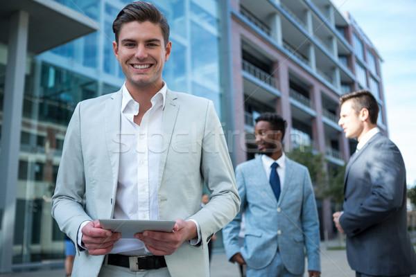 Sorridente empresário digital comprimido prédio comercial retrato Foto stock © wavebreak_media