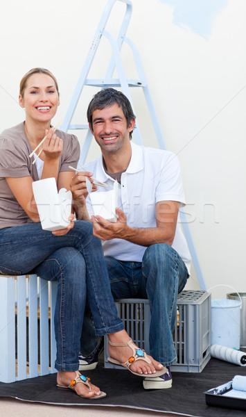 Smiling couple eating while decorating a room Stock photo © wavebreak_media