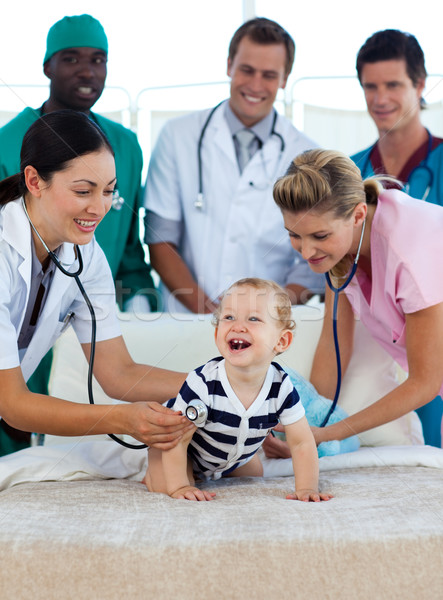 Smiling baby with a medical team in hospital Stock photo © wavebreak_media
