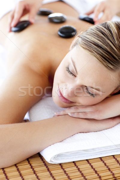 Stock photo: Glad woman receiving a massage with hot stone in a spa center