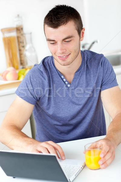 Charmant jeune homme utilisant un ordinateur portable jus d'orange cuisine Photo stock © wavebreak_media