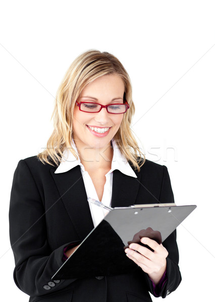 Serious businesswoman wearing glasses taking notes in her clipboard against a white background Stock photo © wavebreak_media
