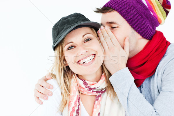 young man with hat whispering something to his female friend against a white background Stock photo © wavebreak_media