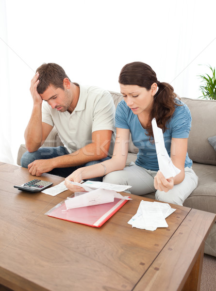 Worried couple looking at their bills in the living room at home Stock photo © wavebreak_media