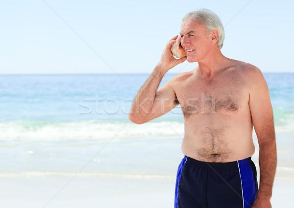 Kıdemli adam dinleme kabuk plaj gökyüzü Stok fotoğraf © wavebreak_media
