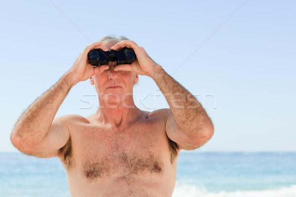 Senior homem pássaro assistindo praia azul Foto stock © wavebreak_media