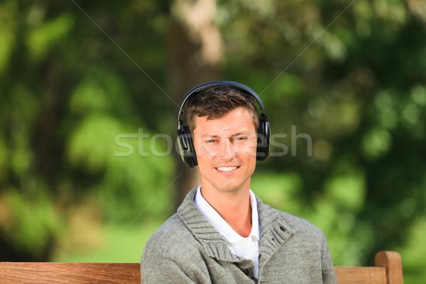 молодым человеком прослушивании музыку скамейке технологий расслабиться Сток-фото © wavebreak_media