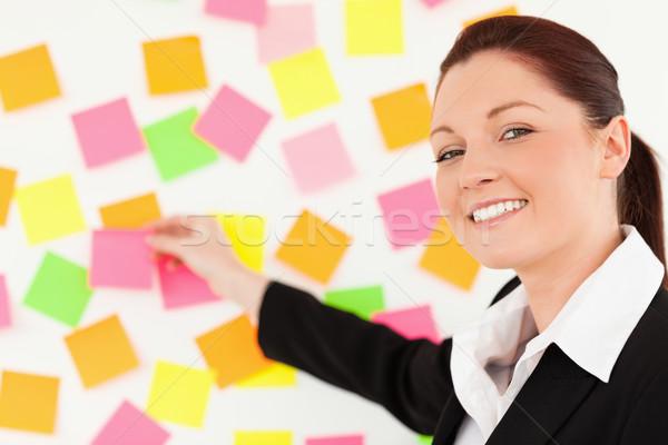 Aranyos nő jegyzetek fehér fal iroda Stock fotó © wavebreak_media