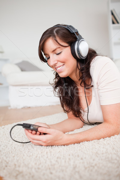 Pretty brunette woman listening to music with her mp3 player while lying on a carpet in the living r Stock photo © wavebreak_media