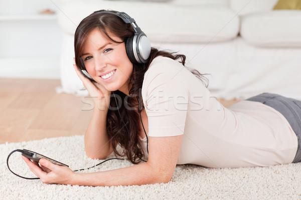 Stockfoto: Aantrekkelijk · brunette · vrouwelijke · luisteren · naar · muziek · mp3-speler · tapijt