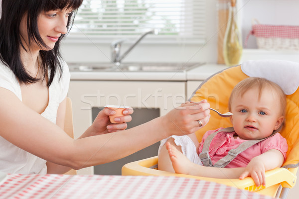 Stock photo: Attractive brunette woman feeding her baby while sitting in the kitchen