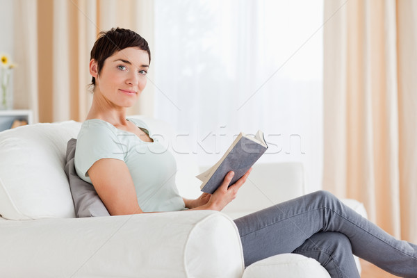 Short-haired brunette holding a book while looking at the camera Stock photo © wavebreak_media