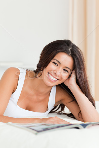 close up of a smiling woman lying on bed reading a magazine looking into camera in bedroom Stock photo © wavebreak_media