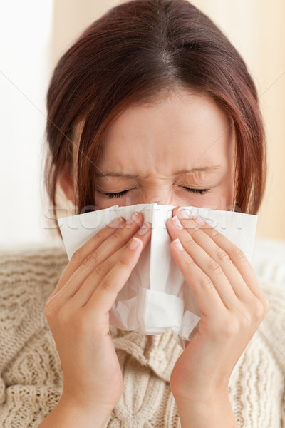 Sneezing young woman in a living room Stock photo © wavebreak_media