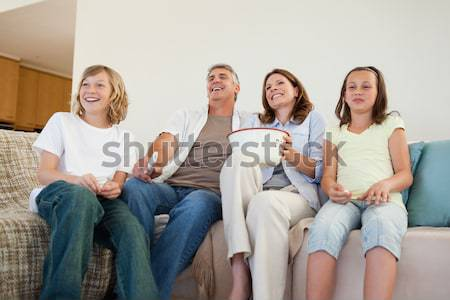 Stock photo: Cheering Women watching a movie eating popcorn in living room