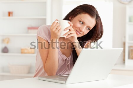 Stock photo: A lovely young woman with a cup of coffee looking to the screen of her laptop