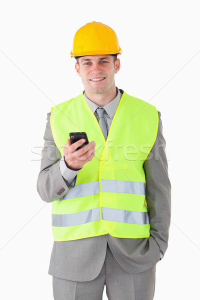 Portrait of a young builder holding his cellphone against a white background Stock photo © wavebreak_media