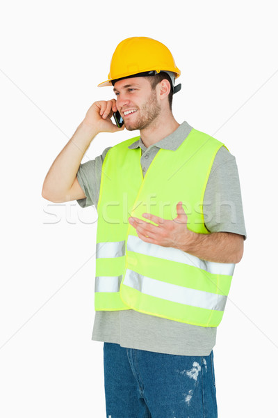Smiling young construction worker discussing on the cellphone against a white background Stock photo © wavebreak_media