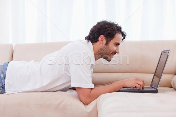 Handsome man using a laptop in his living room Stock photo © wavebreak_media