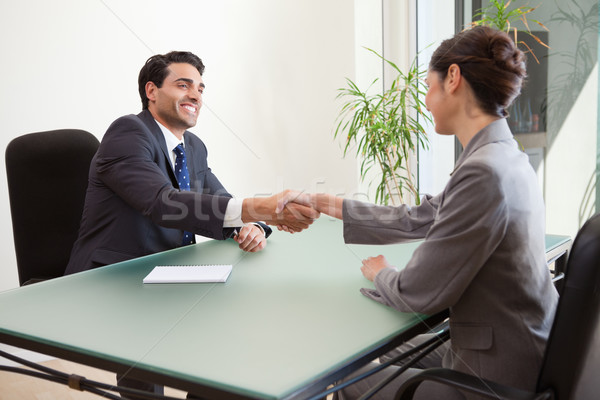 Smiling manager interviewing a good looking applicant in his office Stock photo © wavebreak_media