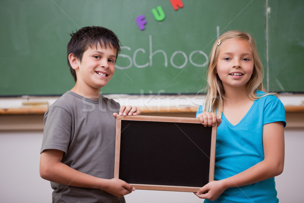 Pupils holding a school slate in a classroom Stock photo © wavebreak_media