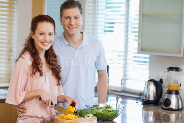 Stock photo: Smiling couple in the kitchen preparing salad