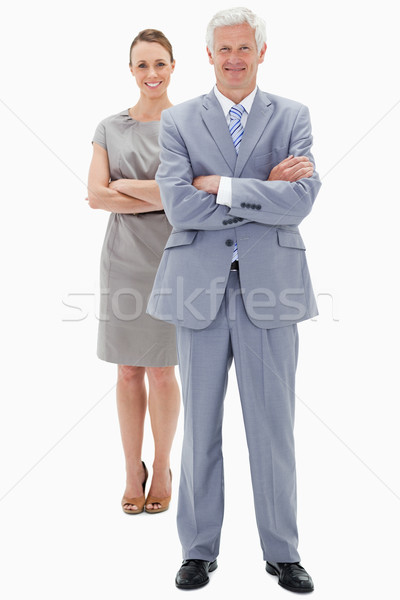 White hair businessman with a woman in background smiling and crossing their arms against white back Stock photo © wavebreak_media