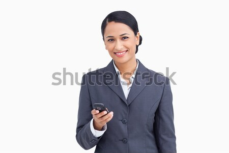 Close up of smiling saleswoman holding cellphone against a white background Stock photo © wavebreak_media