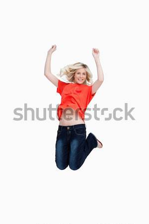 Fair-haired teenager energetically jumping and raising her arms above the head Stock photo © wavebreak_media