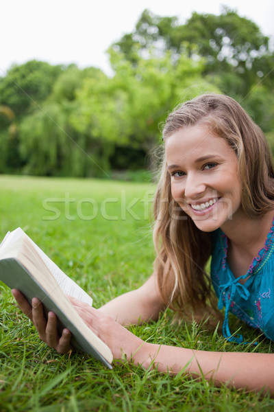Happy student lying on the grass in the countryside while holding a book Stock photo © wavebreak_media