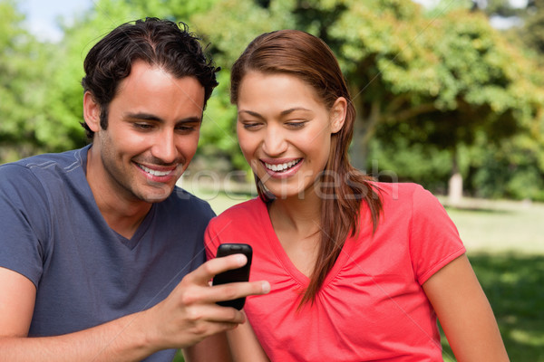 Two friends smiling as they are looking at something on a mobile phone while sitting in a bright gra Stock photo © wavebreak_media