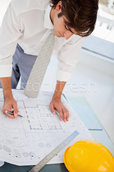 A man with a pen in hand is hard at work on some blueprints for work Stock photo © wavebreak_media