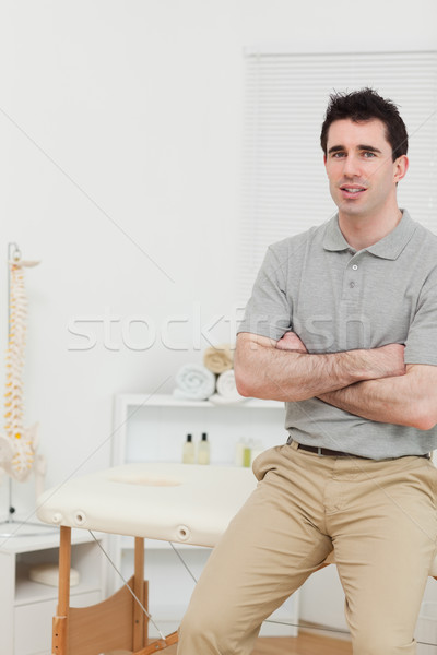 Peaceful osteopath sitting with arms crossed in his medical room Stock photo © wavebreak_media